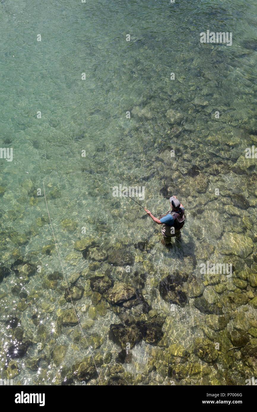 A fly-fisherman casts off in clear waters of the Sava Bohinjnka river, on 18th June 2018, in Bohinjska Bela, Bled, Slovenia. Stock Photo