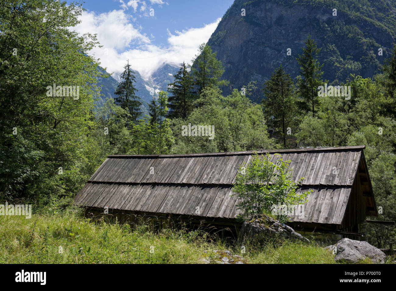With the highest peaks in Slovenia in the distance is a traditional Slovenian mountain hut in the Slovenian Julian Alps, on 22nd June 2018, in Trenta, Triglav National Park, Slovenia. Beyond are the mountains, Kreiski 2050m, Pihavec 2419m, Dolina Zadnjica and Triglav 2864m. Stock Photo
