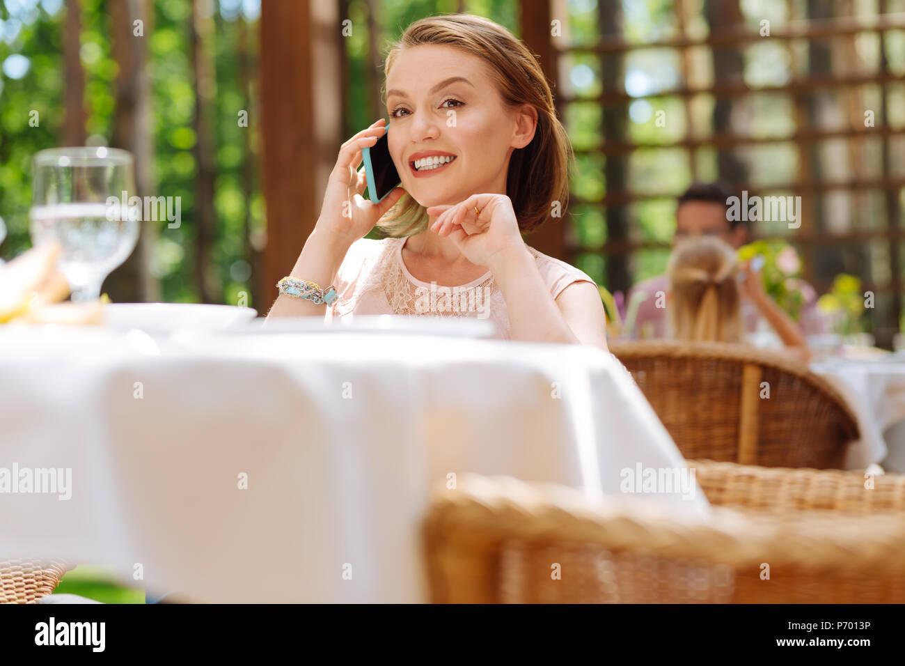 Prosperous businesswoman calling her partner - Stock Image