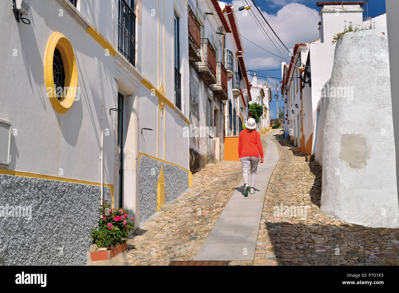 Woman with red pullover walking along small cobble stone alley inbetween medieval white washed houses - Stock Image