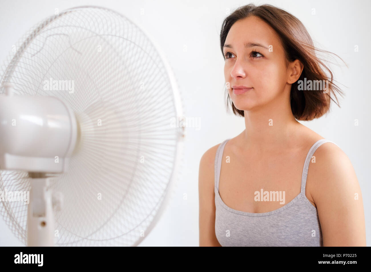 Young girl trying to refresh and cooling against summer haze - Stock Image