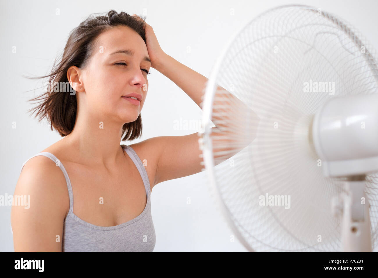 Woman refreshing in front of a electric fan ventilator - Stock Image