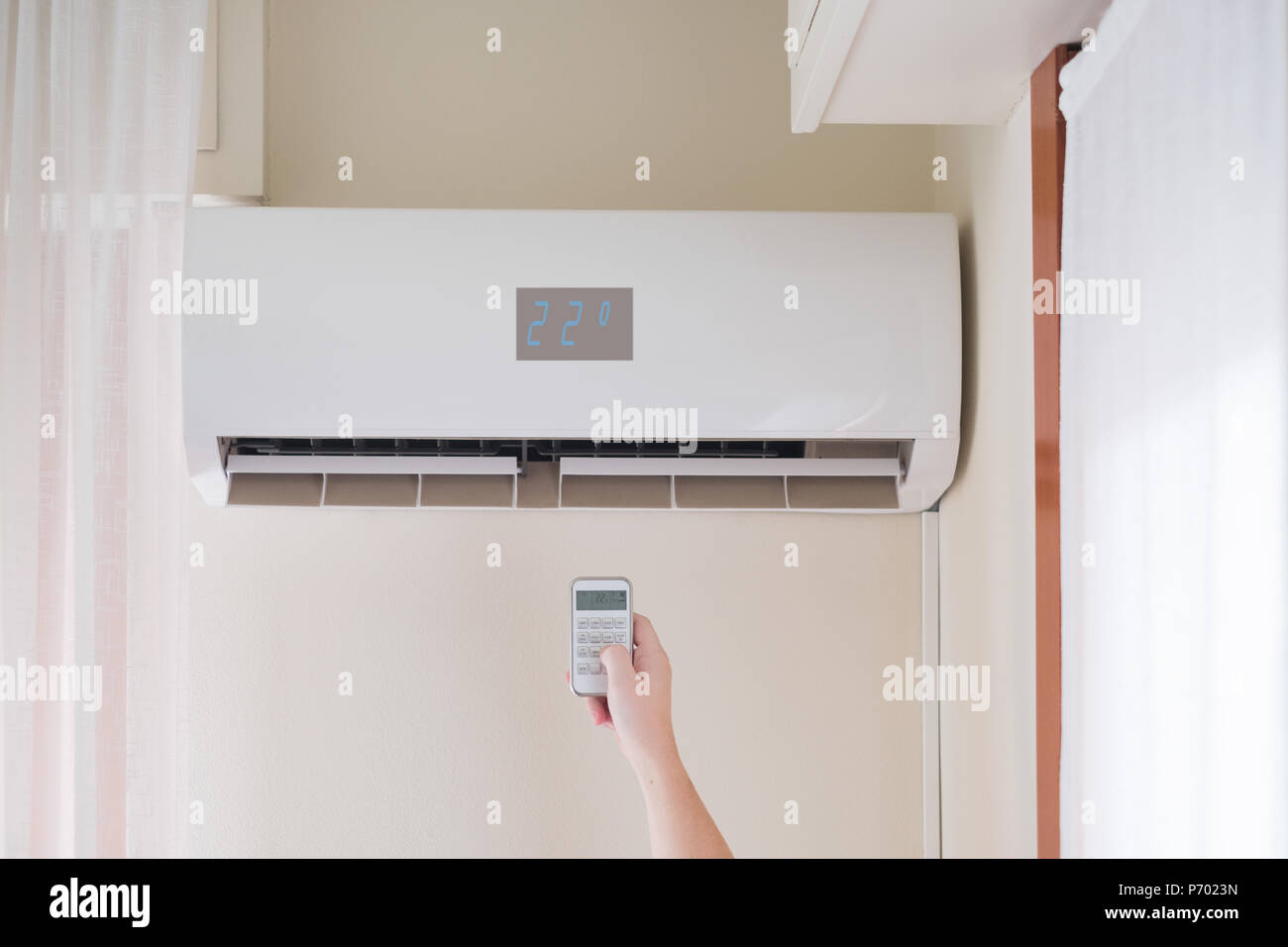 Air conditioner mounted on the room wall and temperature remote control - Stock Image