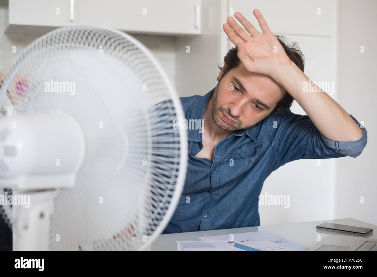 Sweaty man trying to refresh from heat with a fan - Stock Image