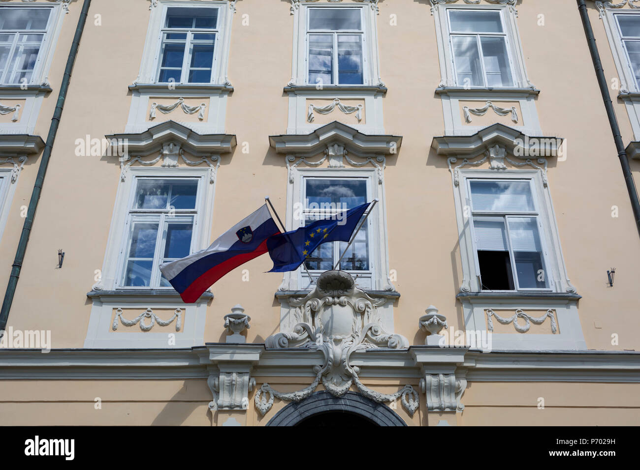 The Slovenian and the European Union flags hang together outside a building in the Slovenian capital, Ljubljana, on 27th June 2018, in Ljubljana, Slovenia. - Stock Image