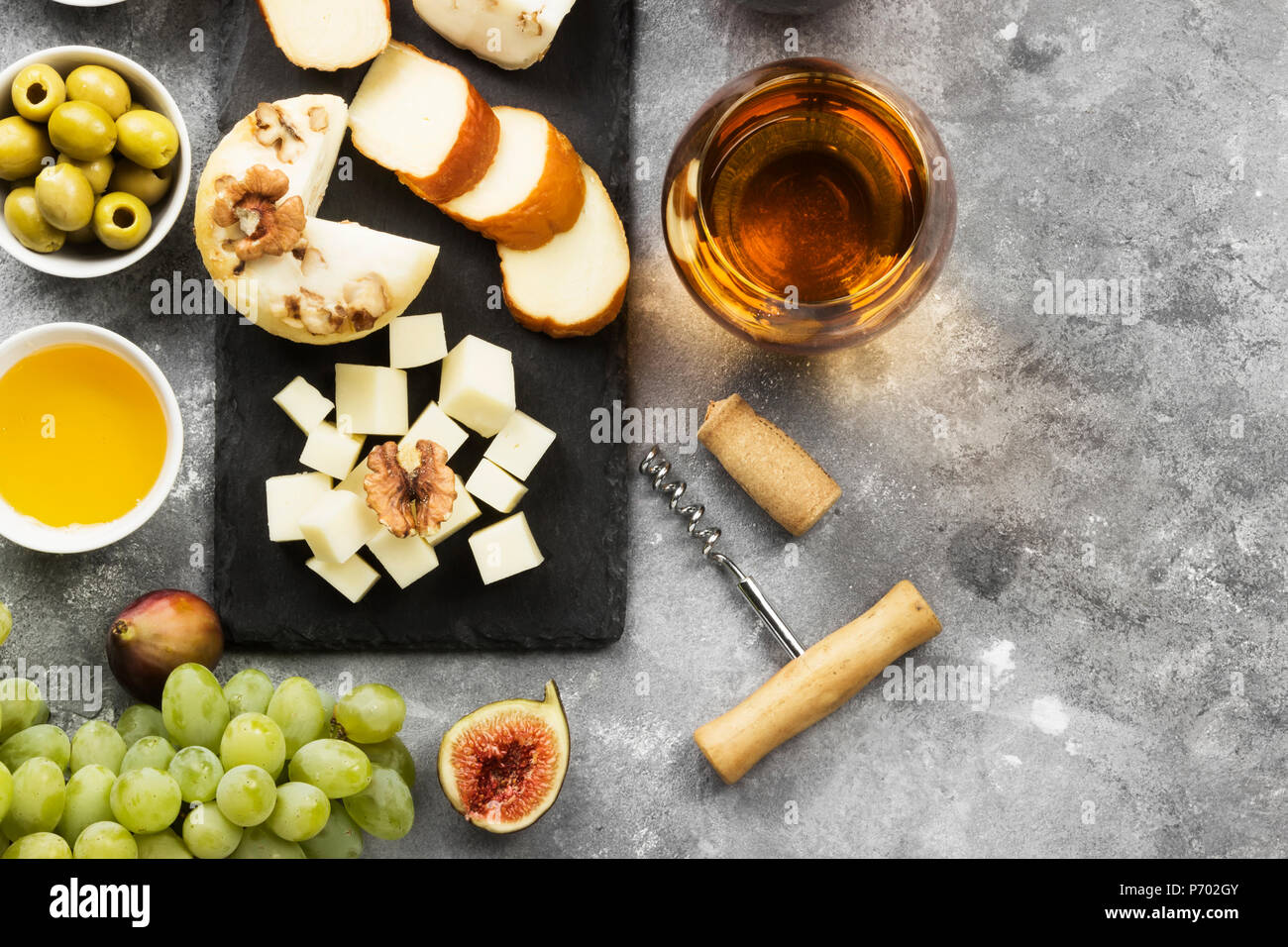 Snacks with wine - various types of cheeses, figs, nuts, honey, grapes on a gray background. Top view, copy space. Food background Stock Photo