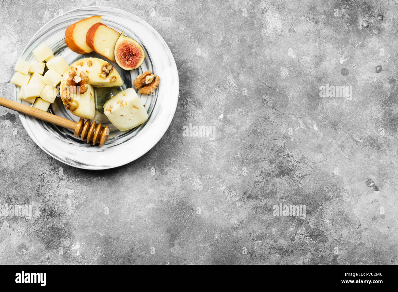 Snacks with wine - various types of cheeses, figs, nuts, honey on a gray background. Top view, copy space. Food background Stock Photo