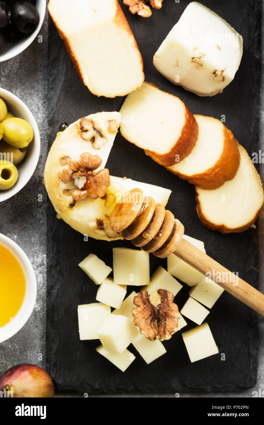 Snacks with wine - various types of cheeses, figs, nuts, honey, grapes on a gray background. Top view. Food background Stock Photo