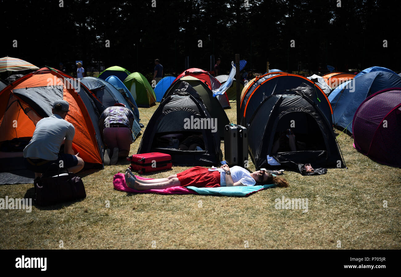 A women snoozes in the queue on day two of the Wimbledon Championships at the All England Lawn Tennis and Croquet Club, Wimbledon. - Stock Image