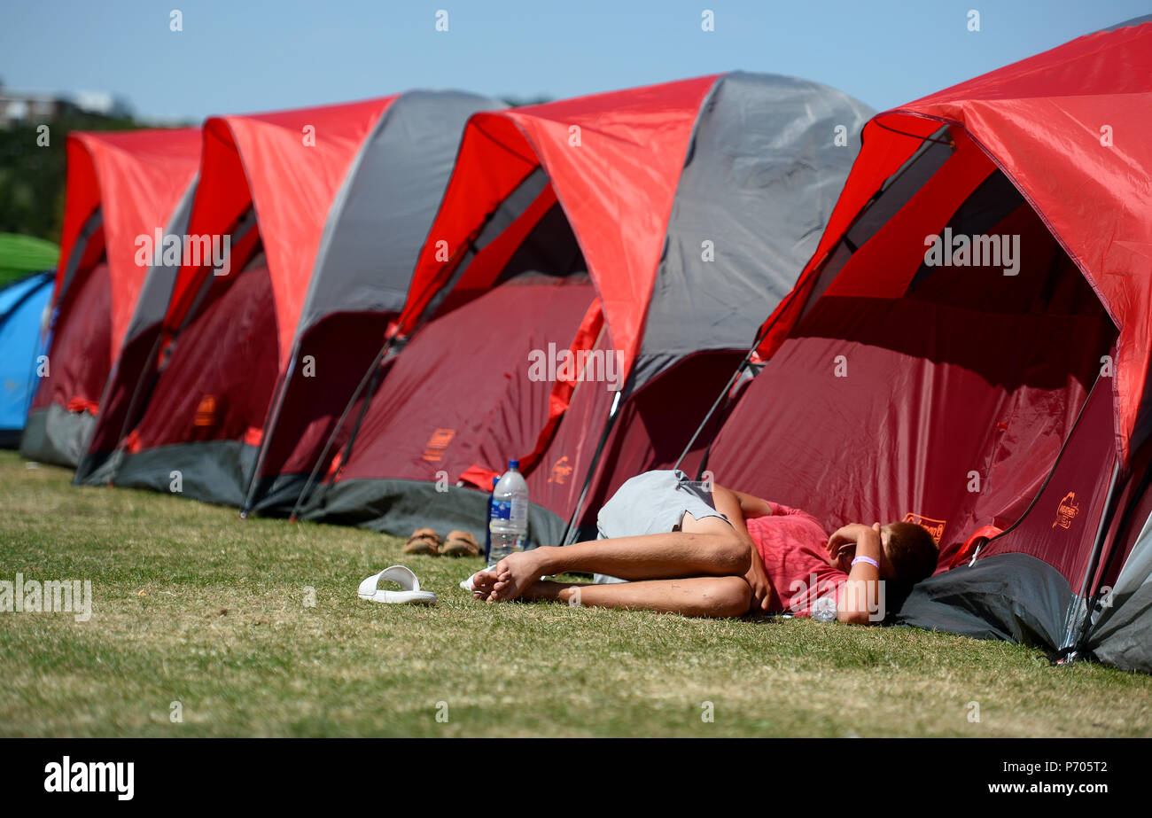A man snoozes in the queue on day two of the Wimbledon Championships at the All England Lawn Tennis and Croquet Club, Wimbledon. - Stock Image