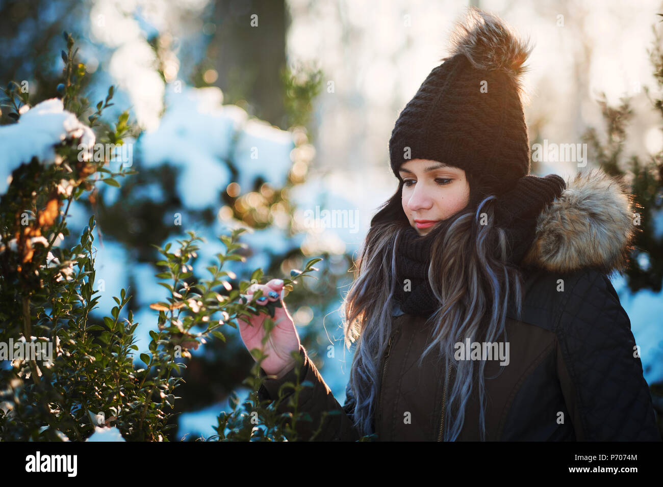 Young woman touch bush leaves outdoor winter portrait - Stock Image