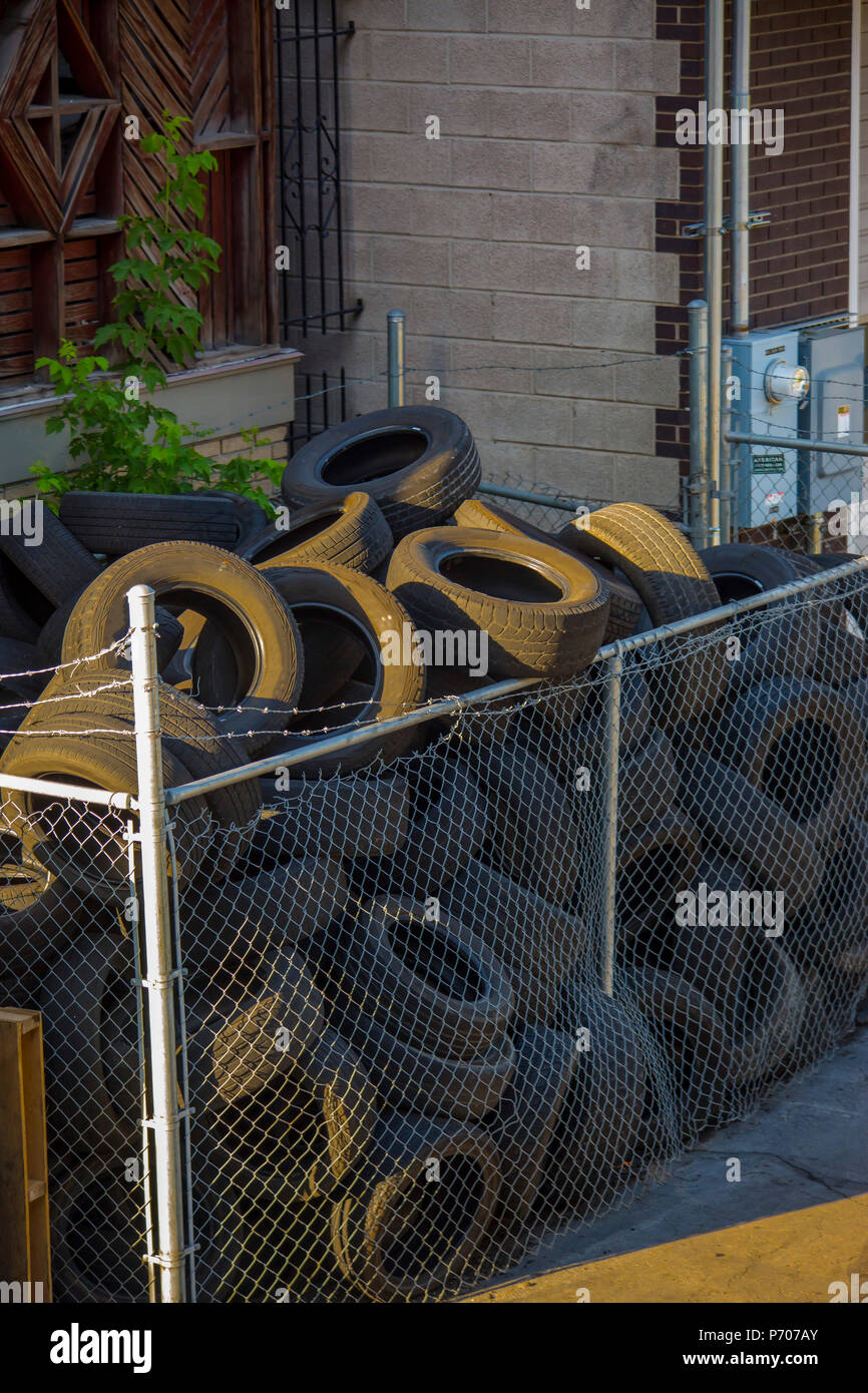 Trashed tires illuminated by late-day sun - Stock Image