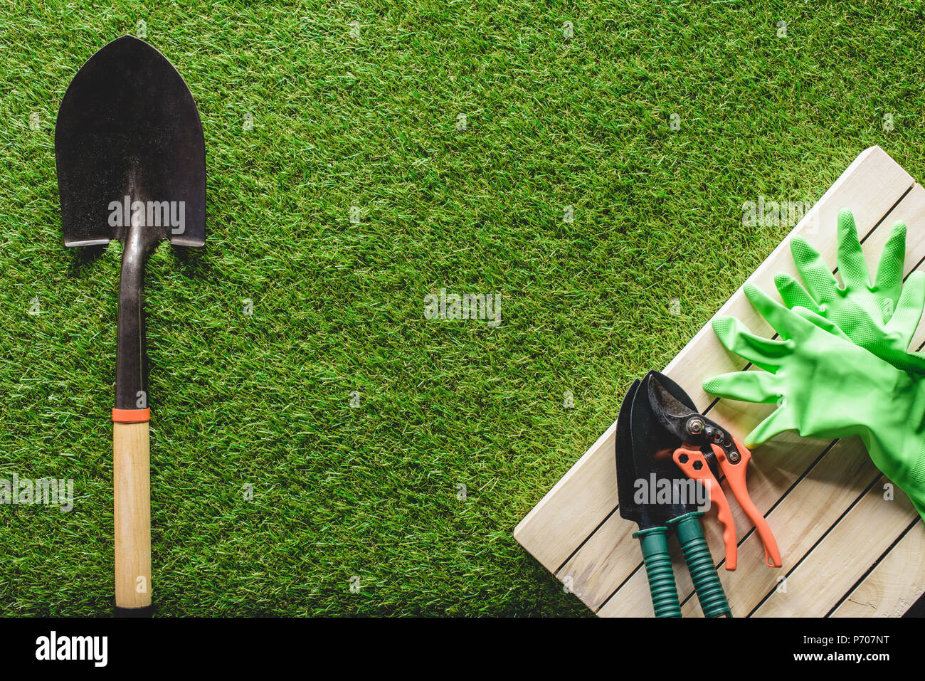 Top View Of Gardening Tools And Protective Gloves On Grass Stock