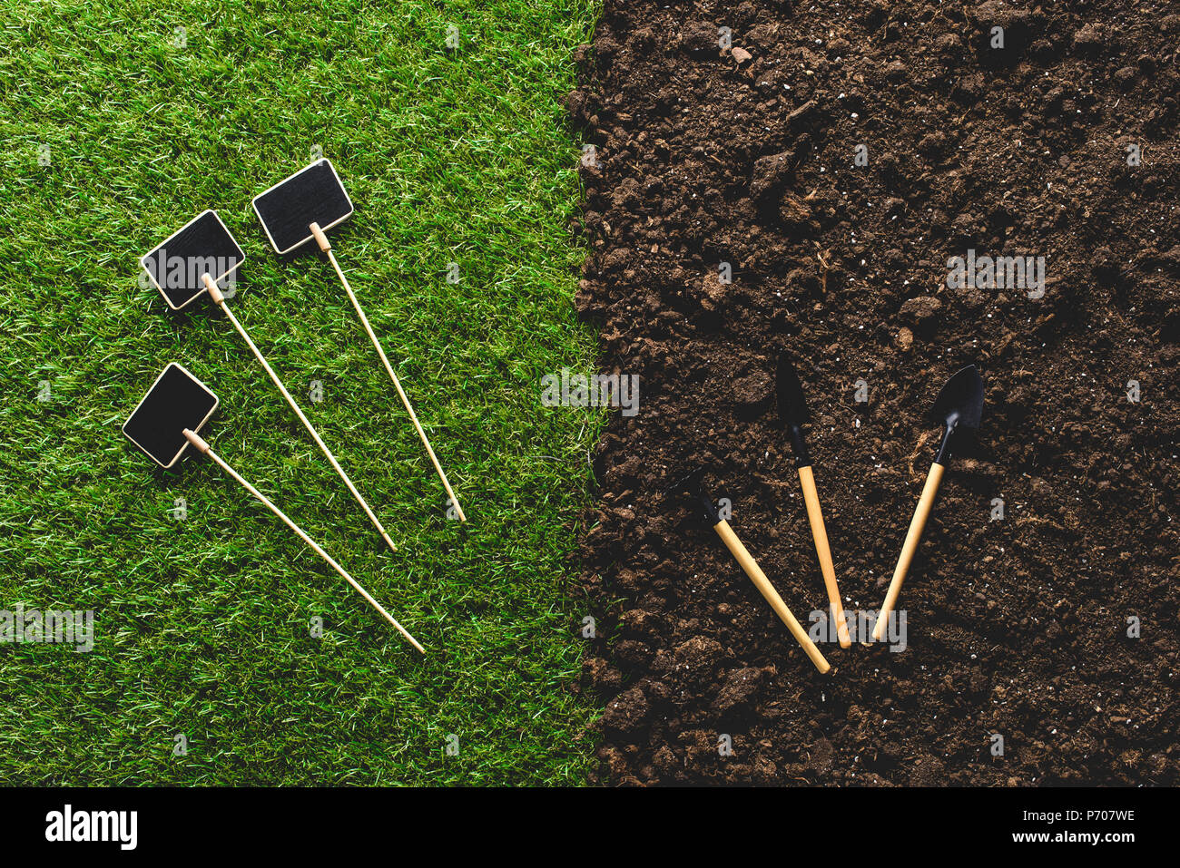 top view of empty blackboards on grass and gardening tools on soil - Stock Image