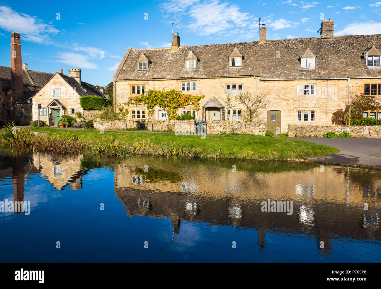 Traditional Cotswold cottages and a water mill reflected in the river Eye, Lower Slaughter, Gloucestershire, UK - Stock Image