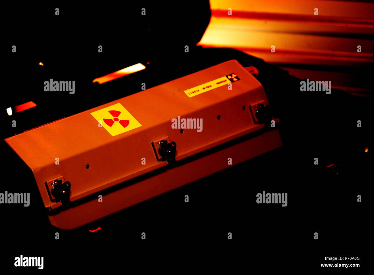 Box shaped metal container with radiation warning in a military grade transport box under red light - Stock Image