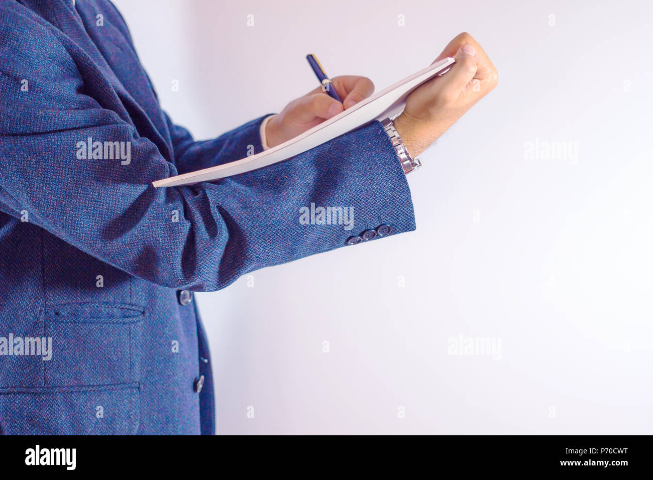Close-up of businessman written on paper on white background / businessman is writing a letter or signing a agreement. - Stock Image