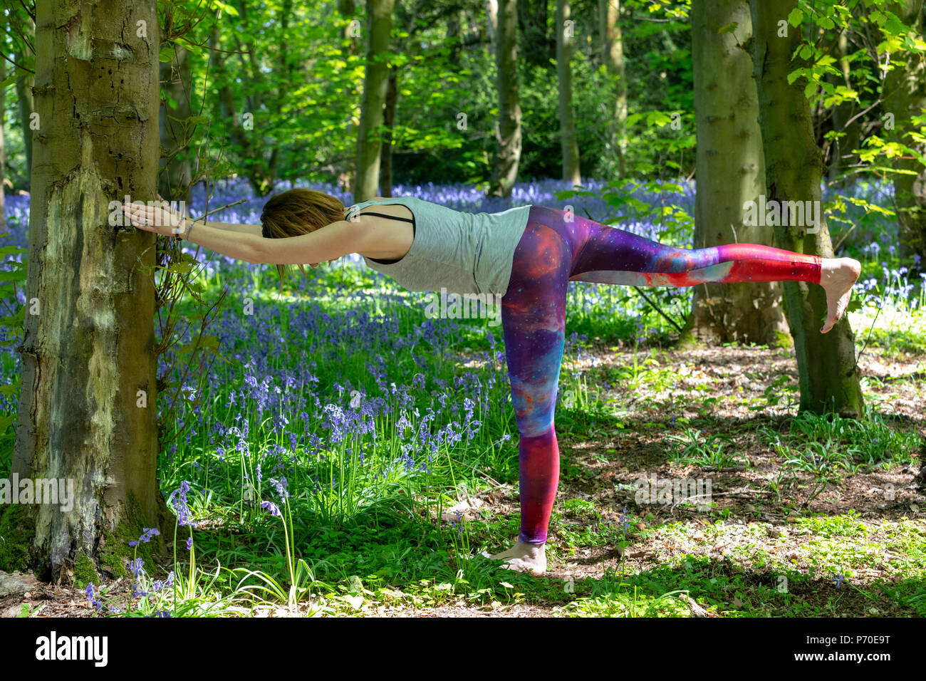 A yoga instructor demonstrates yoga poses during an outdoor yoga