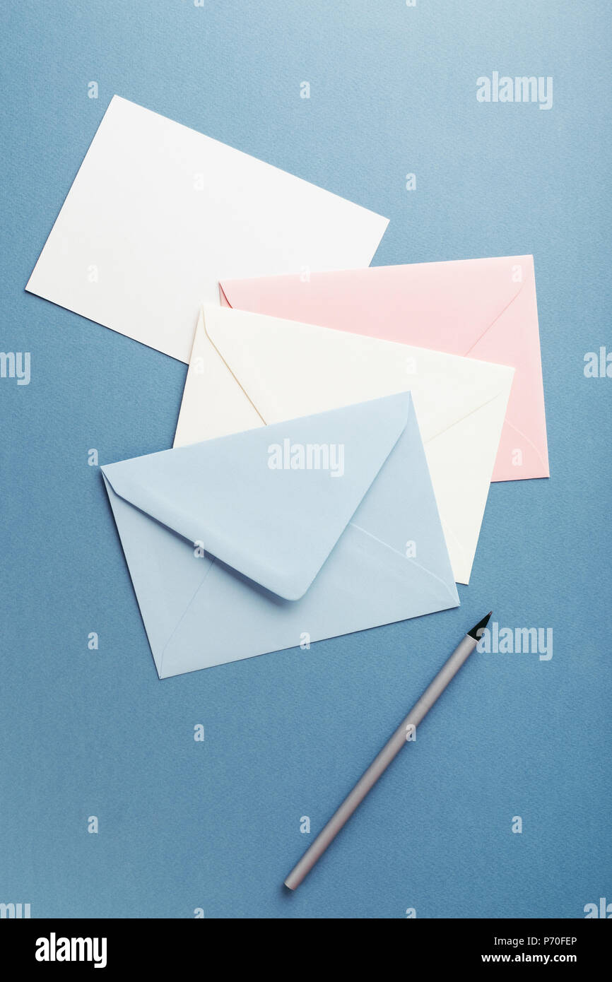 Group of colorful envelopes on blue table with empty card. Correspondence concept. Mockup. - Stock Image