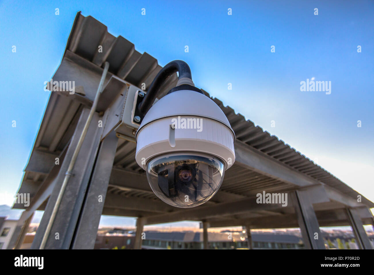 White dome security camera in business lot - Stock Image