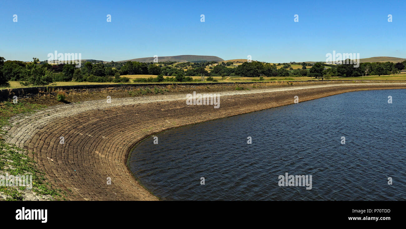 Barrowford reservoir overlooked by Pendle Hill on Tuesday 3.7.18 showing the low water levels. This reservoir feeds the Leeds and Liverpool canal. - Stock Image
