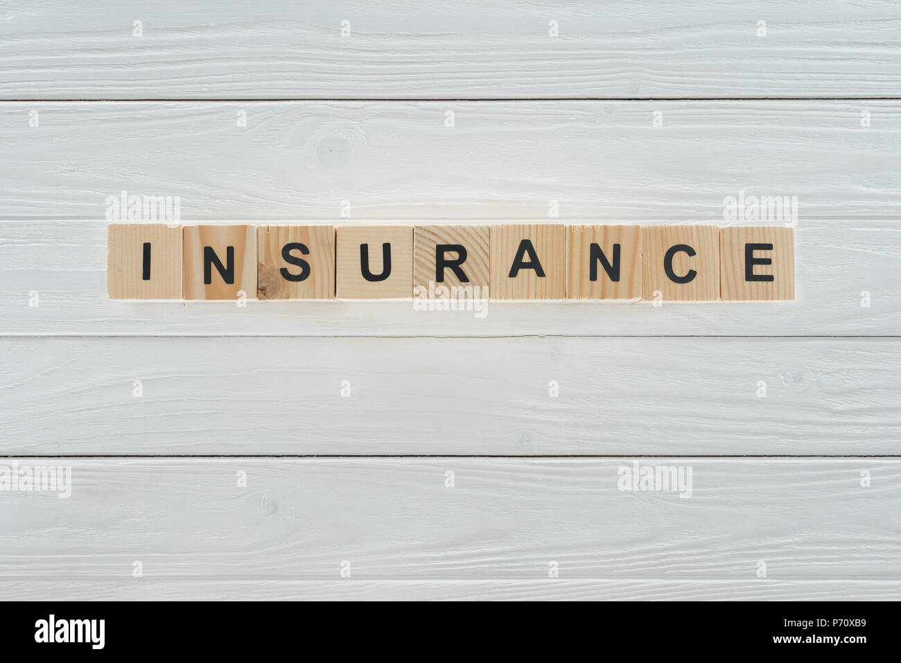 top view of insurance word made of wooden blocks on white wooden surface Stock Photo