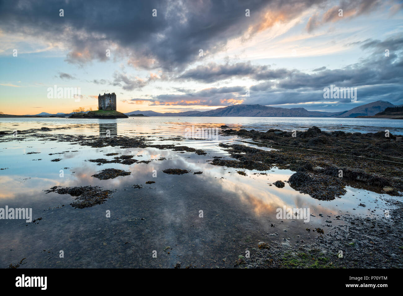 Sunset over Castle Stalker on the shores of Loch Linnhe near Appin in Scotland - Stock Image