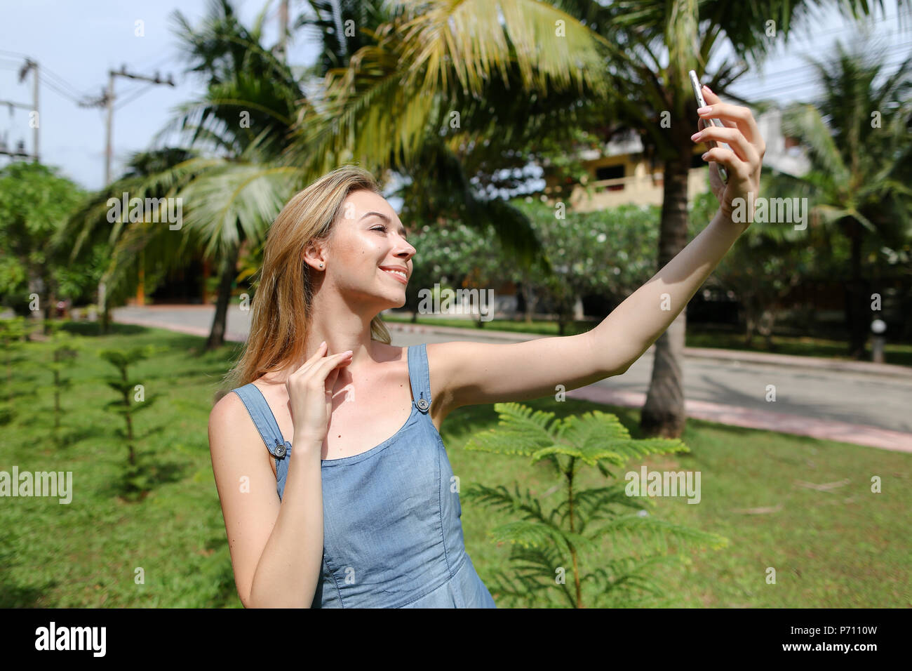 Young pretty woman making selfie by smartphone with palms in background. - Stock Image