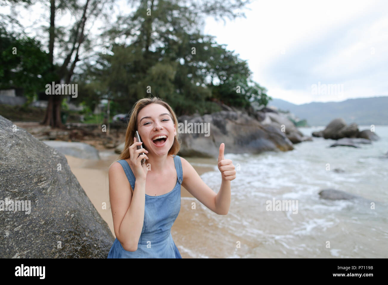 Young blonde woman sitting on sand near sea and stones, talking by smartphone and showing thumbs up. - Stock Image