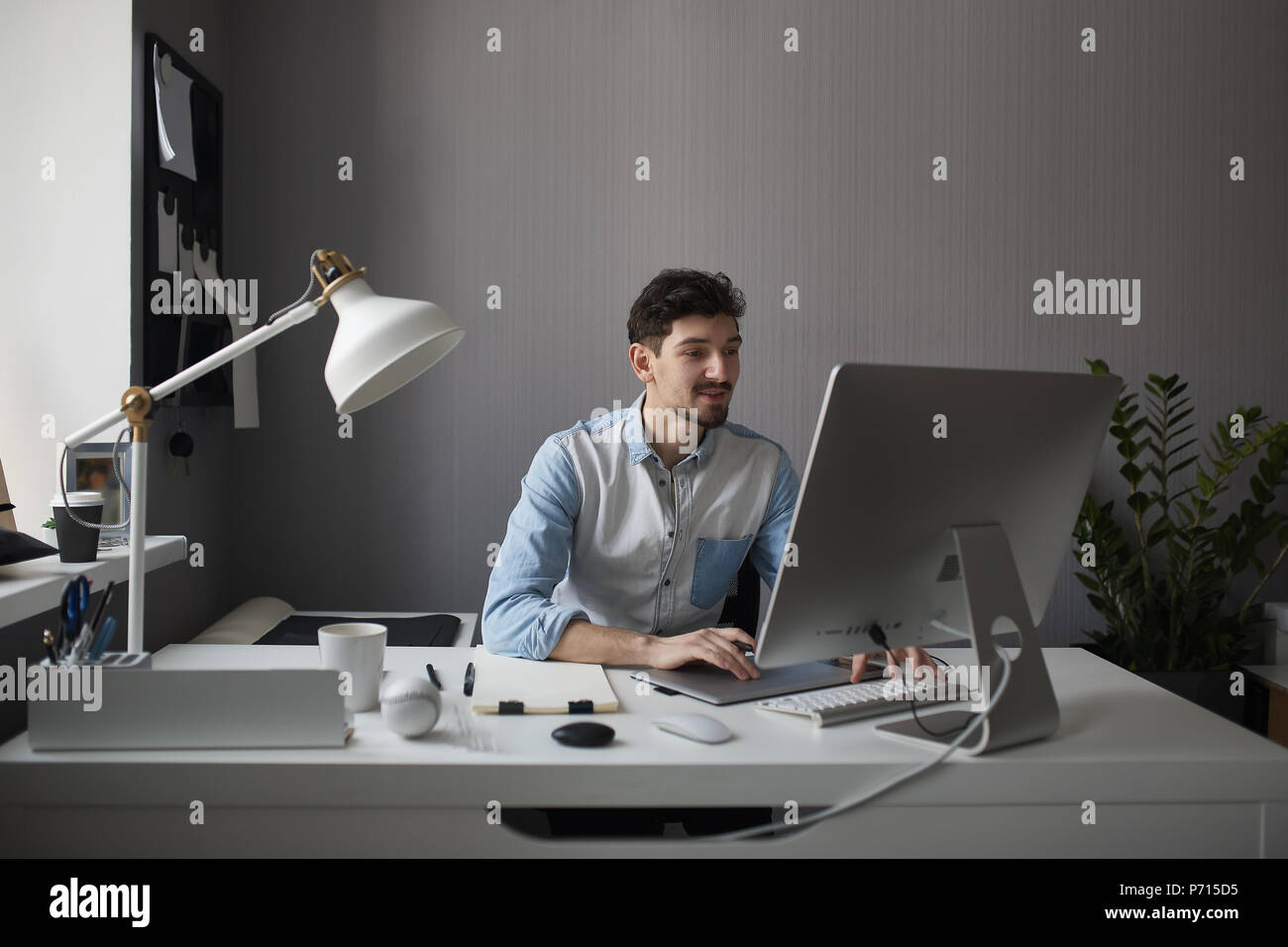 Young male designer using graphics tablet while working with com - Stock Image
