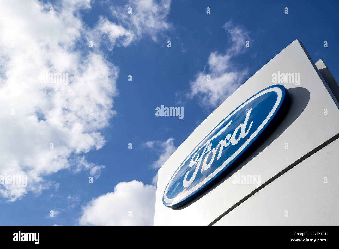 Ford dealership sign against blue sky. Ford is the second-largest U.S.-based automaker. Stock Photo