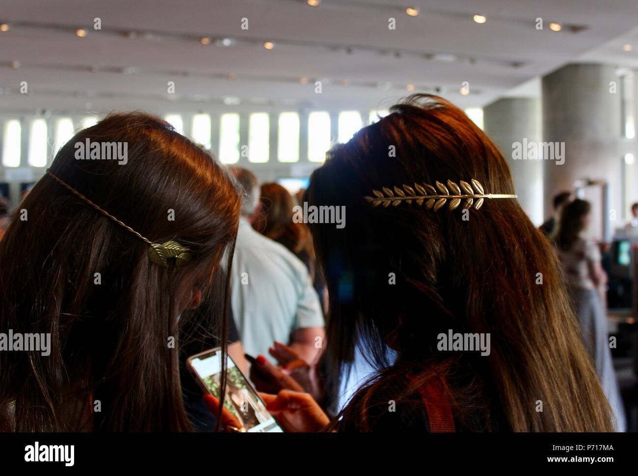 two brunette women with laurel jewellery athens greece on phone - Stock Image