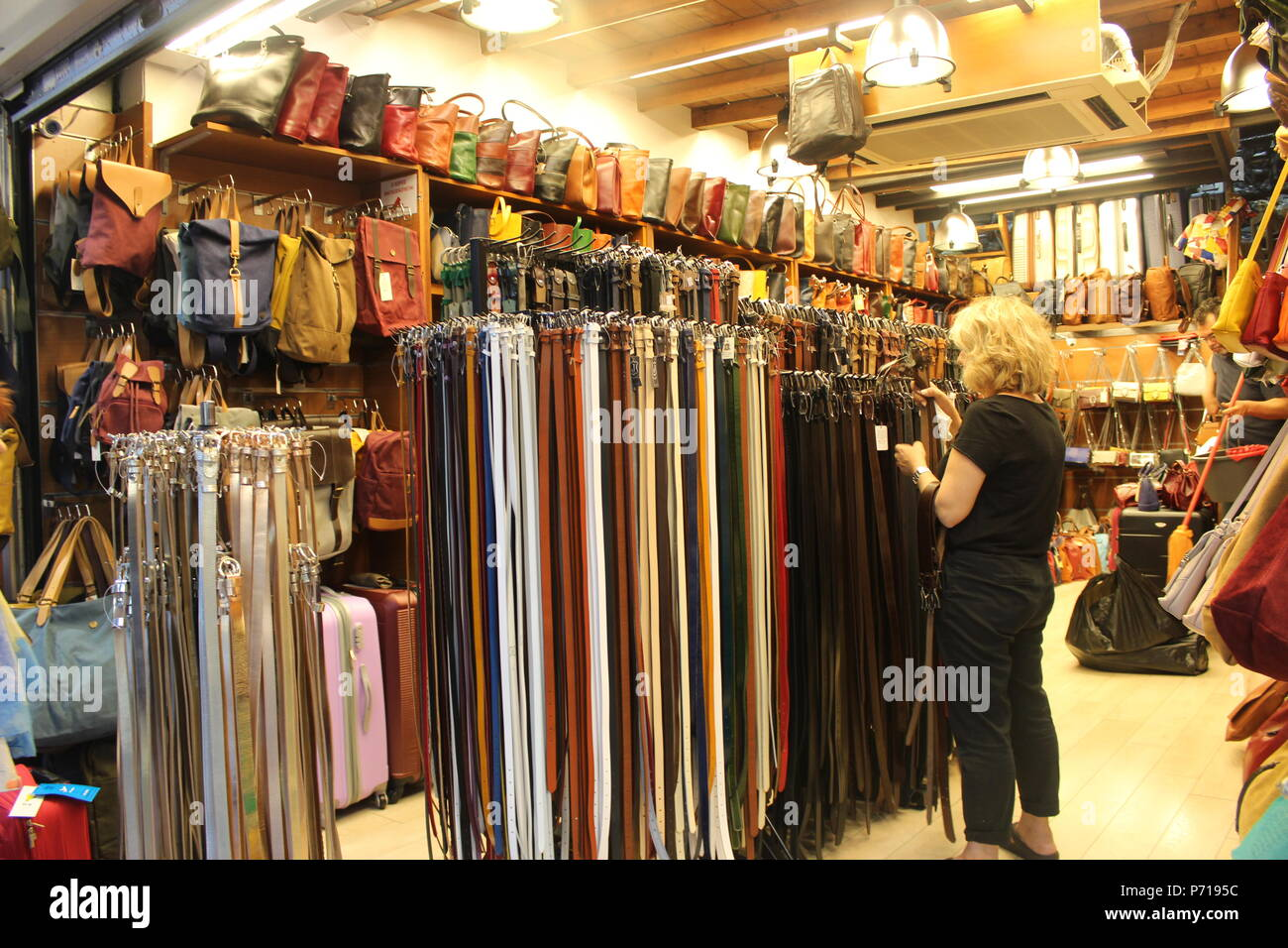 a woman looking at belts in an indoor market stall athens greece - Stock Image