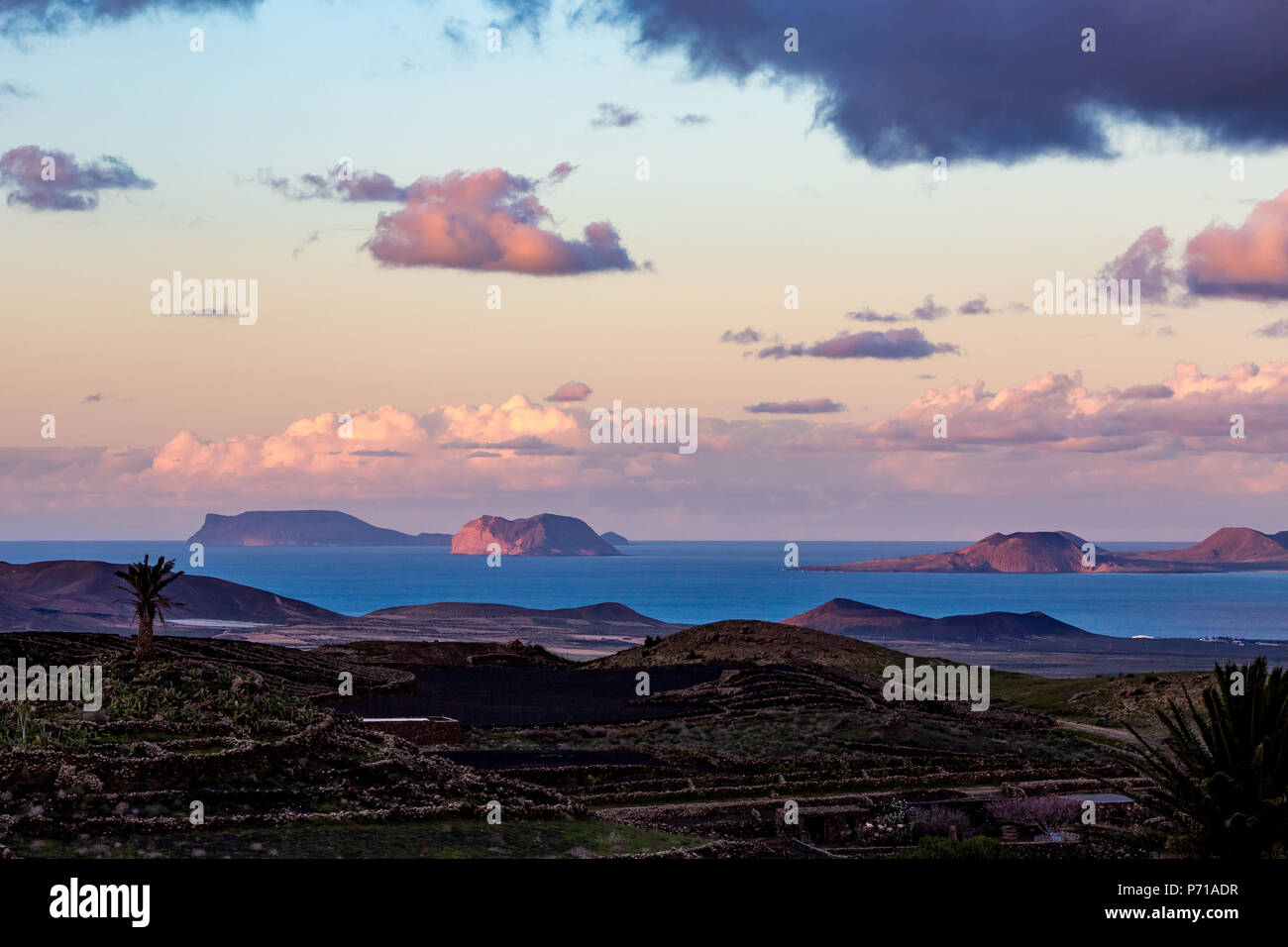 Elevated picturesque blue hour landscape from Lanzarote, high view towards the other Canary islands, Spain, after sunset with expressive sky full with beautiful pink clouds over the Atlantic Ocean - Stock Image