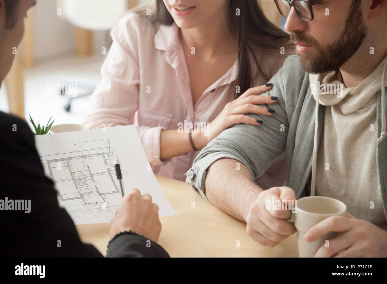 Millennial couple consulting about home design project in archit - Stock Image