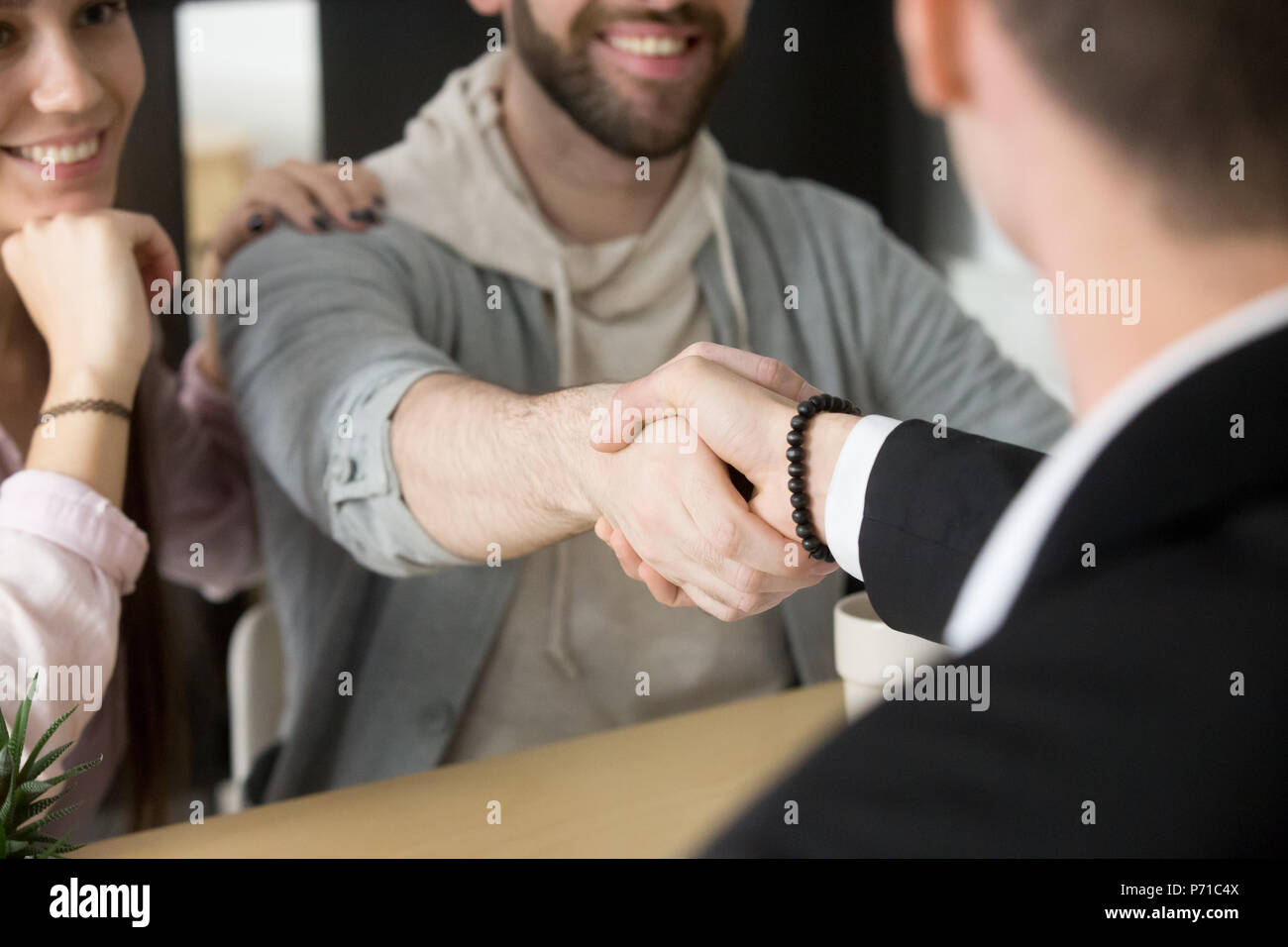 Satisfied couple handshaking realtor closing successful deal - Stock Image