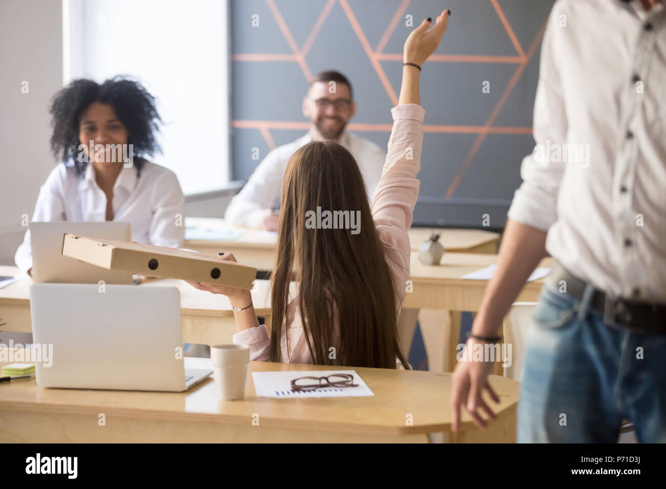 Female employee asking colleagues have dinnertime together - Stock Image