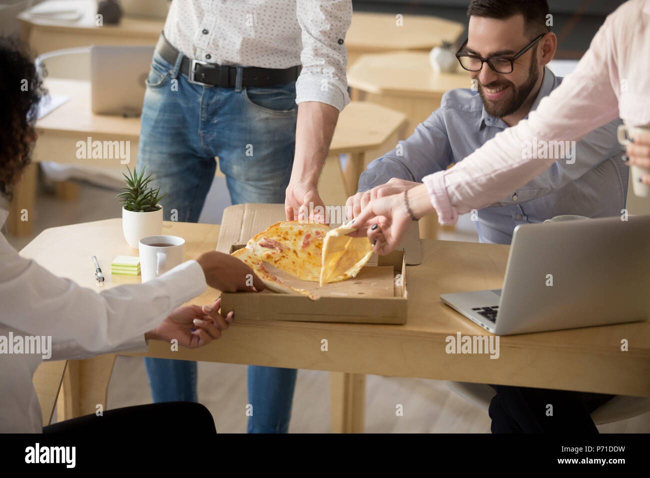 Happy colleagues enjoying shared pizza lunch in office together Stock Photo