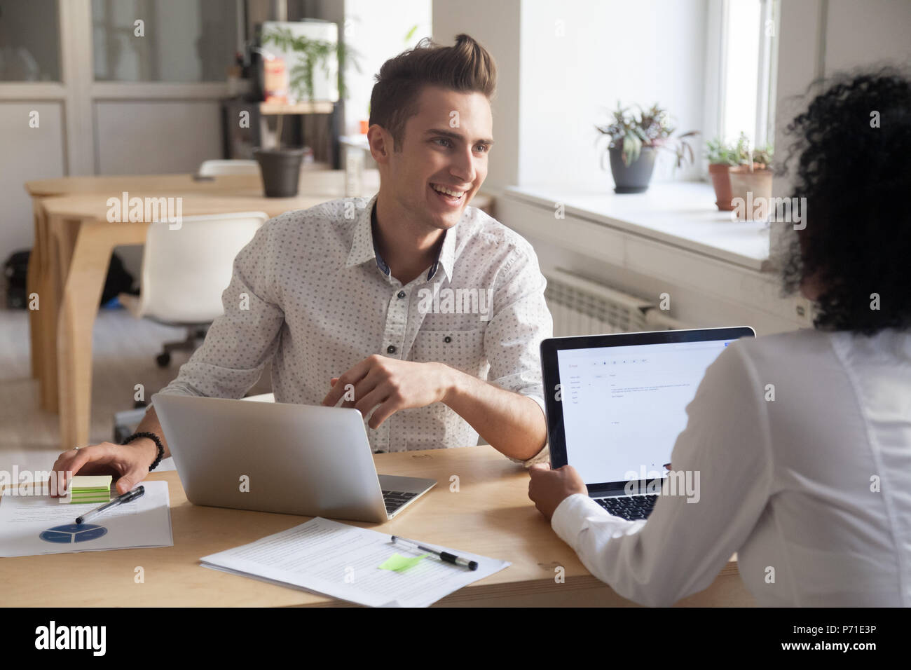 Smiling partners talking brainstorming during office meeting - Stock Image