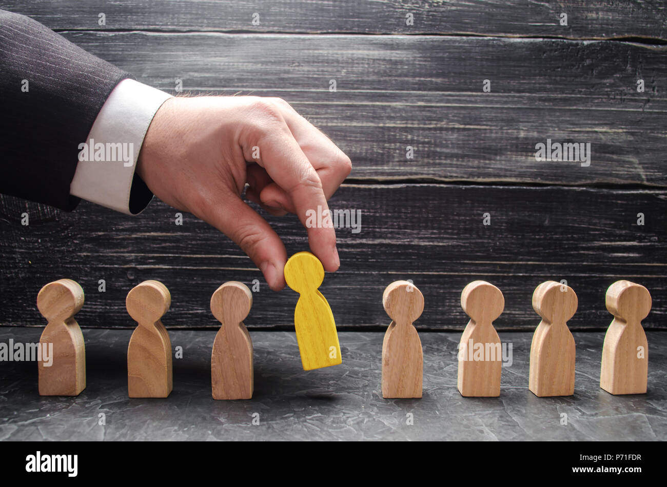 hand of a businessman takes a wooden figure of a man. The concept of search, hiring and firing workers, promotion. Business tactics and strategy, mana - Stock Image