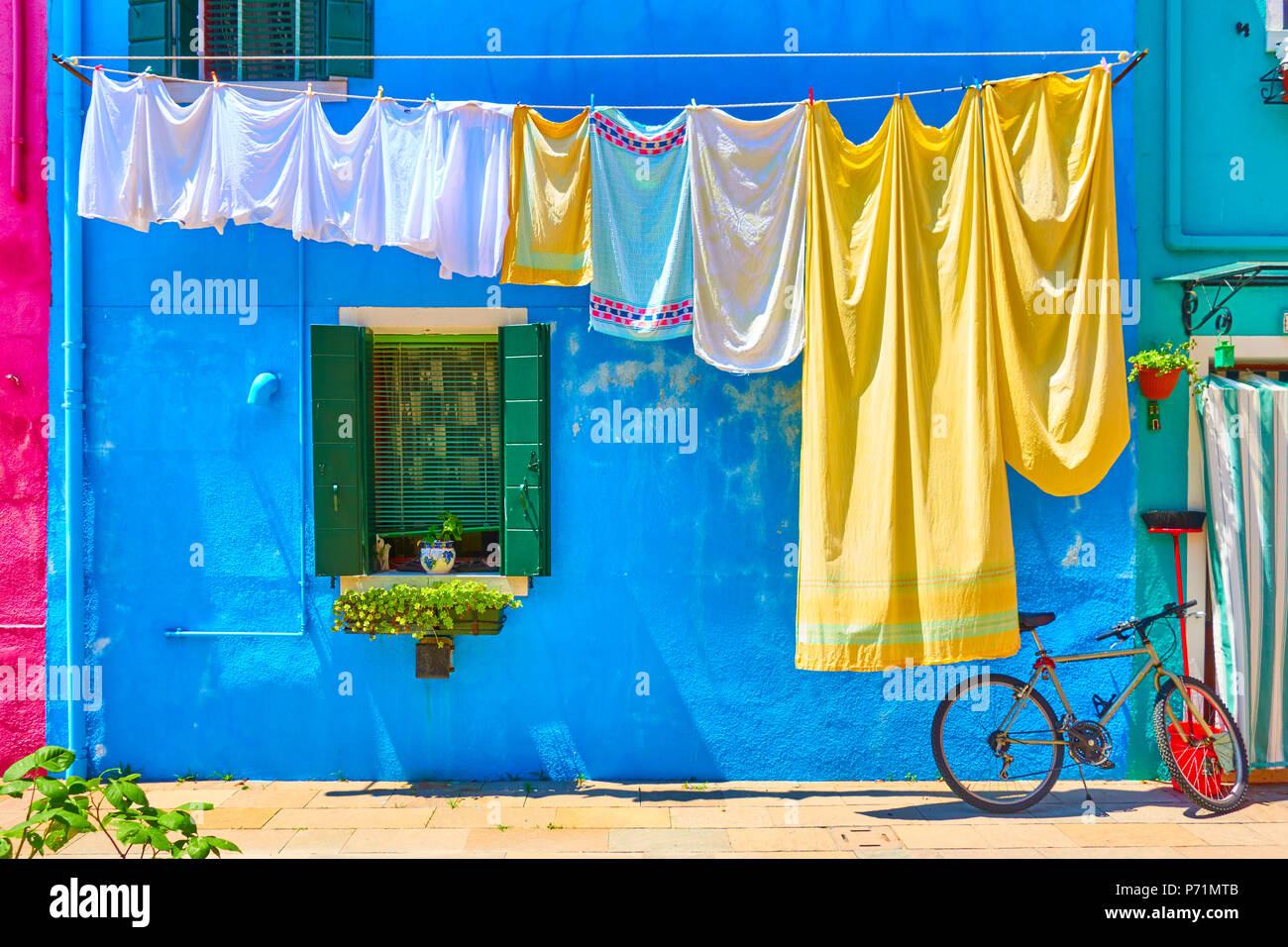 Colorful houses in Burano and airing linen in the street, Venice, Italy - Stock Image
