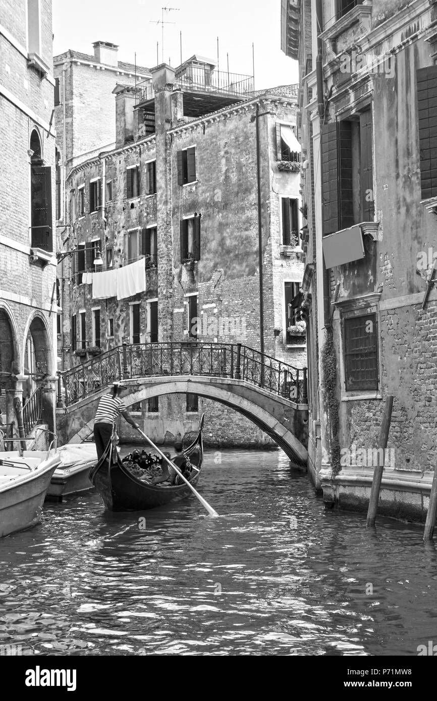 Venetian view with small canal and gondola, Venice, Italy. Black and white - Stock Image
