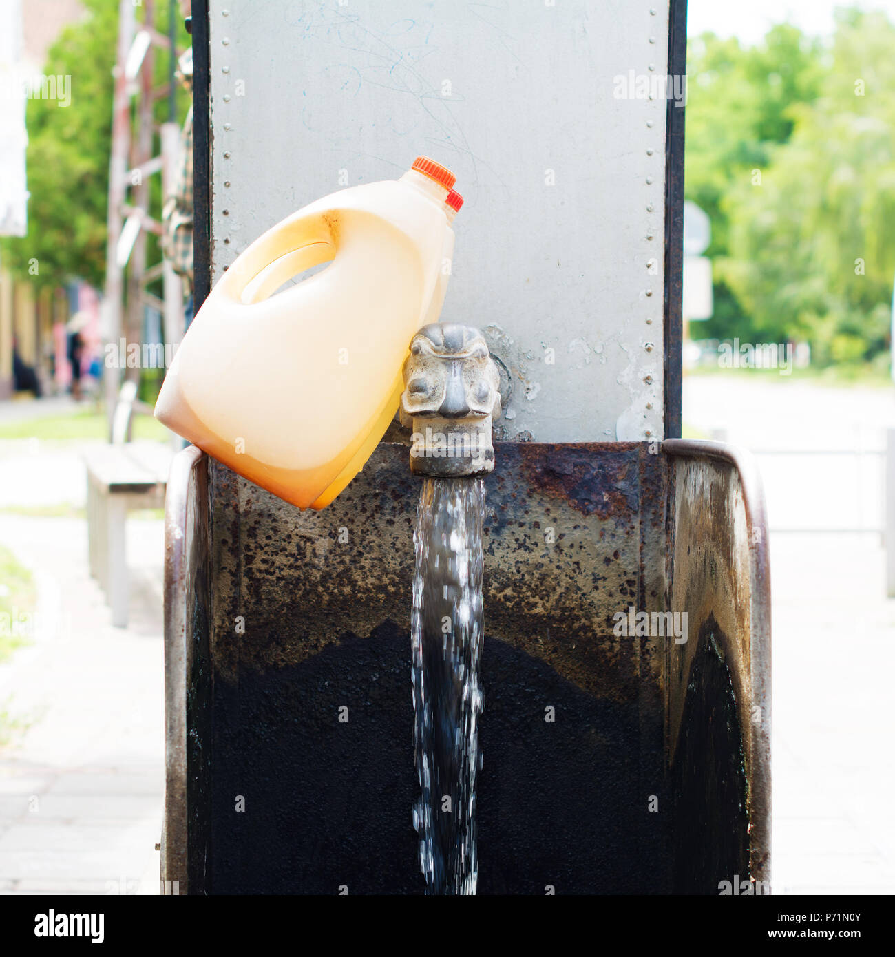 Water fountain installed on a flowing artesian wellhead, for public use. Two plastic demijohns leaned on the spigot. - Stock Image
