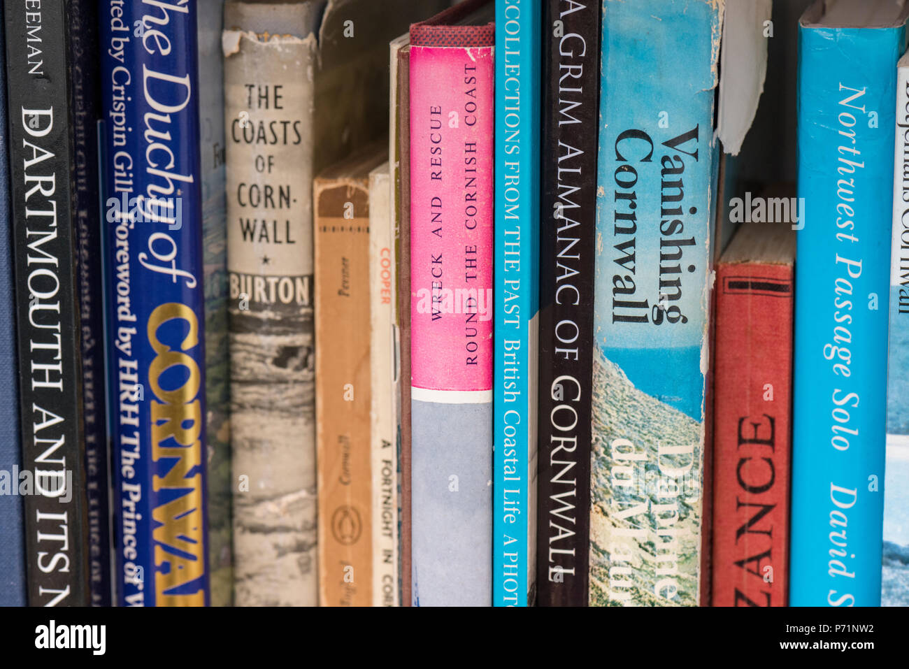 a bookshelf full of books relating to cornwall and travel. - Stock Image