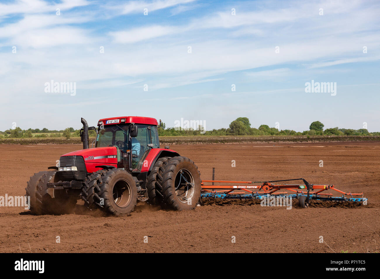 Agricultural tractor pulling the harrow on the peatland to turn over loose milled peat and help it dry out on the sun at the Prosperous Bog in county  - Stock Image