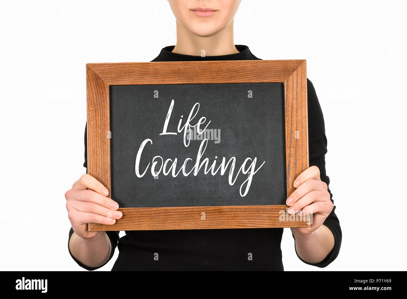 Cropped view of woman holding board with lettering life couching isolated on white - Stock Image