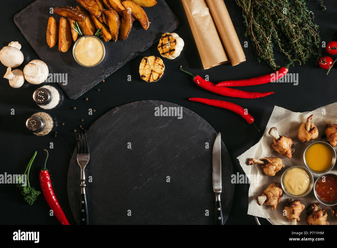 top view of empty slate board with fork and knife, roasted potatoes and vegetables on black Stock Photo