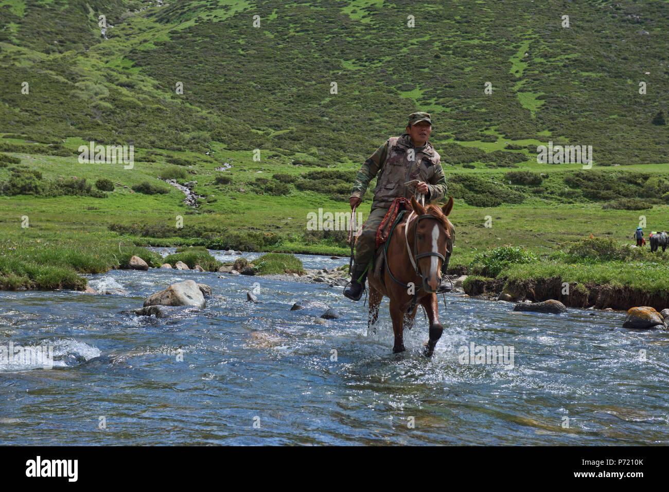 Kyrgyz horserider crossing the Tup River, Jyrgalan Valley, Kyrgyzstan Stock Photo