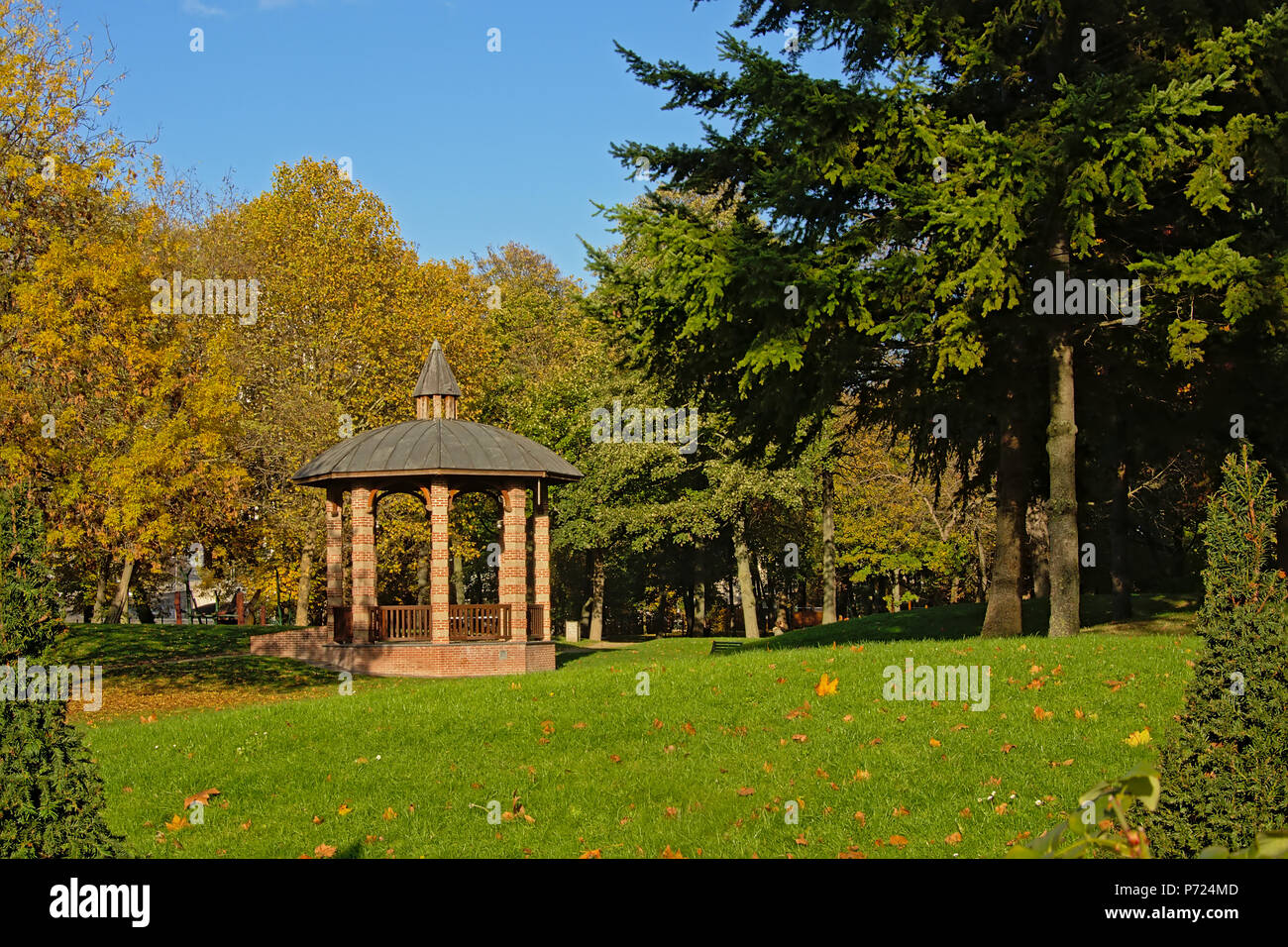 Gazebo in between autumn trees in `Bois de Boulogne` city park on a sunny day with blue sky in Paris, France - Stock Image
