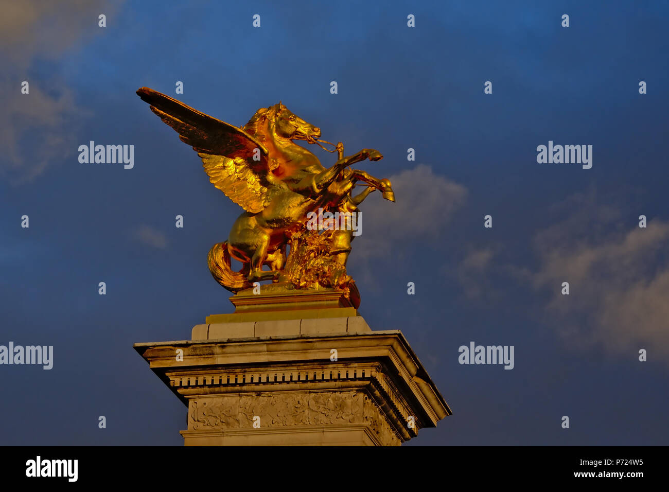 Low angle view on golden pegasus statue on masonry socle in the evening light on Pont Alexandre III bridge in Paris; France - Stock Image